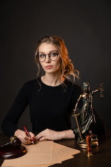 真っ赤な爪が黒い背景の上に孤立して働いている弁護士の女性
