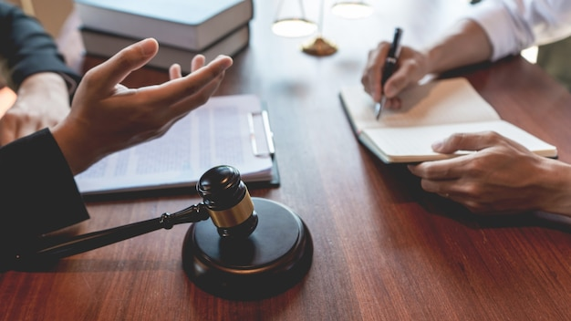 Lawyer working with client discussing about legal legislation in courtroom