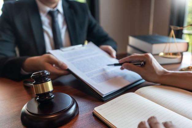 Адвокат, работающий с клиентом, обсуждает правовое законодательство в зале суда