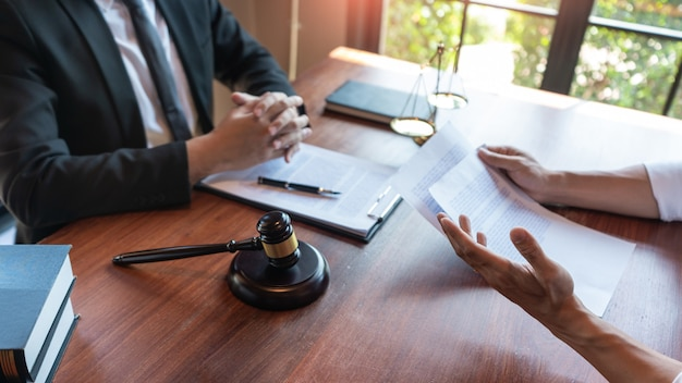 Lawyer working with client discussing contract papers with brass scale