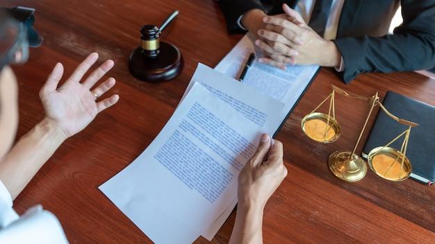 真ちゅう製のスケールで契約書について話し合うクライアントと協力する弁護士