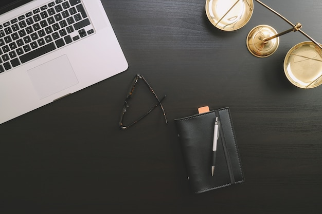 Lawyer workplace with laptop and documents with dark wooden