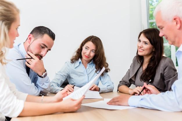 법률 사무소에서 문서를 읽고 계약을 협상하는 팀 회의를 갖는 변호사