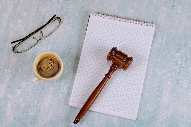 나무 판사 망치가있는 변호사 판사 책상 커피 한 잔, 테이블 사무용품이있는 독서 안경 노트북