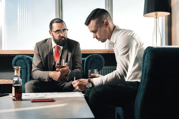 일하는 변호사. 함께 일하면서 위스키를 마시는 두 명의 똑똑한 전문 변호사