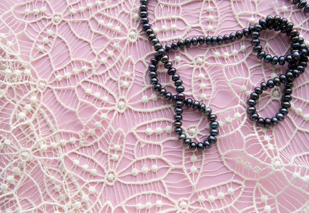Lay flat pink background and the gorgeous lace, glittering necklace of black pearls, and stylish bracelet.