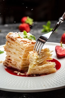 Layer cake napoleon with creamy vanilla swith cream, apples and strawberry jam decorated mint, black background for menu