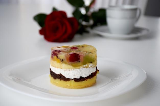Слоеный пирог с фруктами и сливками на белой тарелке перед красной розой и сервиз из чашки и тарелки. день святого валентина завтрак.