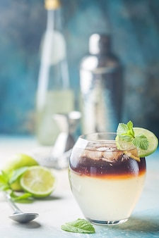 Layer cocktail with rum, cola, lime ang ginger ale over blue background