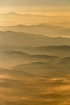 Layer of mountains and mist at sunset time