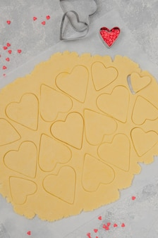 Layer of shortbread dough with cut hearts for valentine's day.