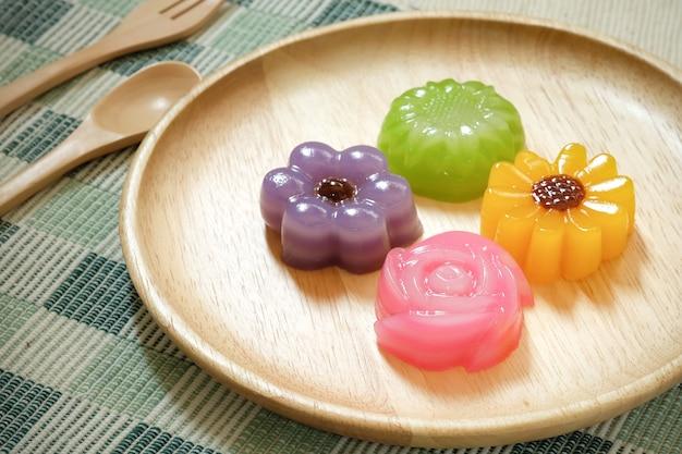 木製のプレート、タイのデザートにレイヤースイートケーキやカノムチャンの花。