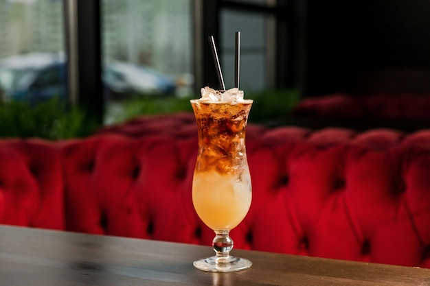 A layered alcoholic cocktail in a hurricane glass, with ice and straw, at the bar