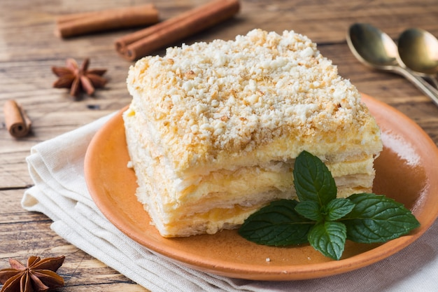 Layered cake with cream napoleon millefeuille vanilla slice with mint on wooden background.