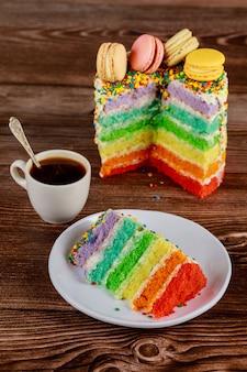 一杯のコーヒーと層状のおいしい自家製レインボーレイヤーケーキ。