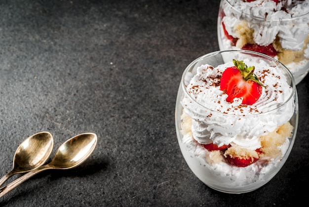 Layered dessert parfait in a glass with strawberries, sponge cake and whipped cream