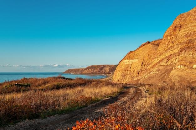 層状の岩層と日没時の海岸への道。ロシア、サハリン島。