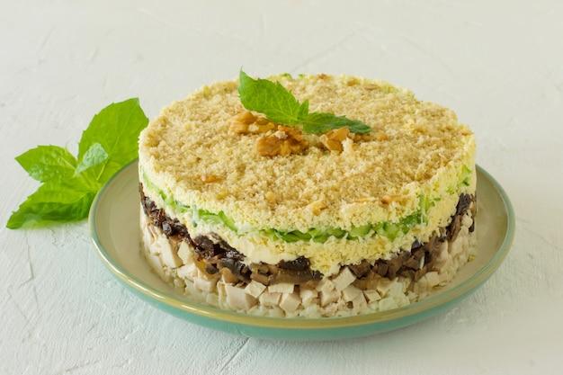 鶏肉、きのこ、プルーン、卵、きゅうり、チーズのレイヤードサラダを白い背景のプレートに添えて、