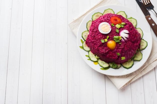 Слоеный салат с сельди и свеклы, морковь и картофель и яйца крупным планом на тарелку.