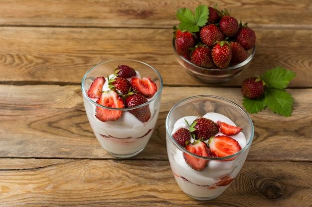 Layered strawberries cream cheese dessert on wooden background