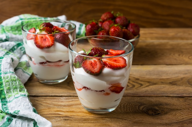 Layered strawberries dessert with cream cheese on rustic wooden background
