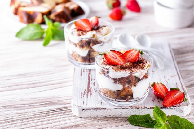 Layered trifle dessert with sponge cake and strawberries