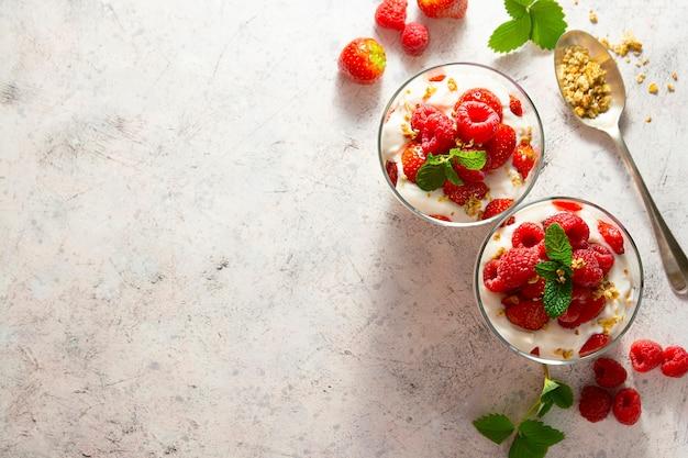 Слоеный йогурт, мюсли и фрукты, клубника и малина. здоровый завтрак