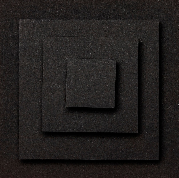 Layers of black squares background flat lay