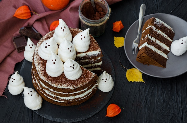 Layers chocolate cake with white chocolate cream and meringue ghosts on top. food idea for halloween party.