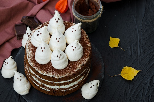 Layers chocolate cake with white chocolate cream and meringue ghosts on top