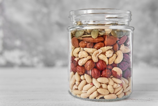 Layers of different types of nuts and seeds in a glass jar close up