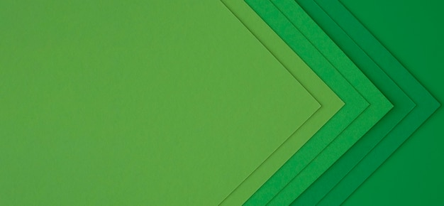 Layers of green papers creating abstract arrows