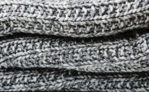 Layers of a knitted gray woolen rolled blanket. close up.