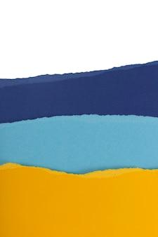 色とりどりの破れた織り目加工の紙シートの層