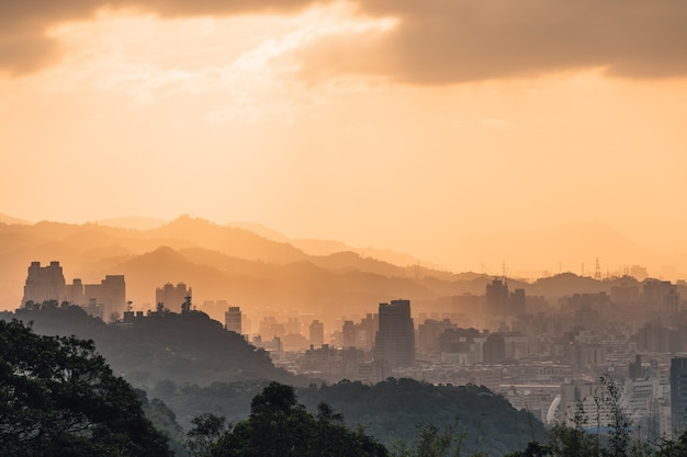 Layers of taipei cityscape and mountains with sunlight when the sun going down.