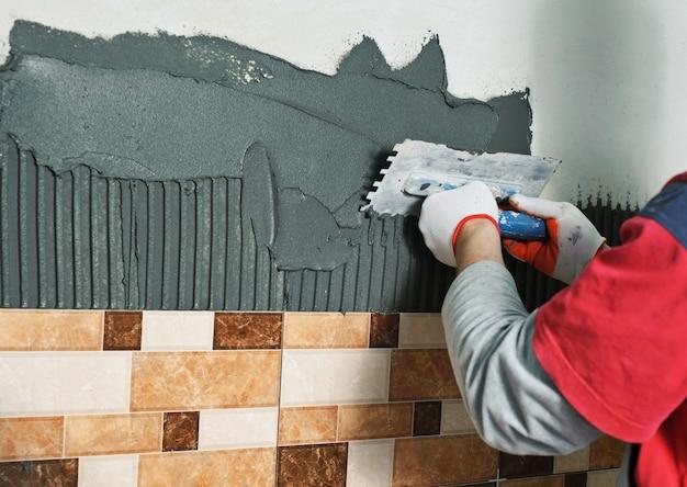 Укладка керамической плитки. плиточник наносит плиточный клей на стену