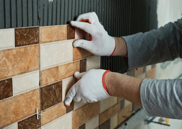 Укладка керамической плитки. плиточник укладывает керамическую настенную плитку на клей