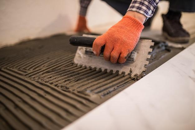 セラミックタイルの敷設。白い床タイルを敷設する準備として、コンクリートの床にモルタルをこすりつけます。