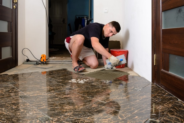 Laying ceramic tiles while repairing in room and applying glue to the floor