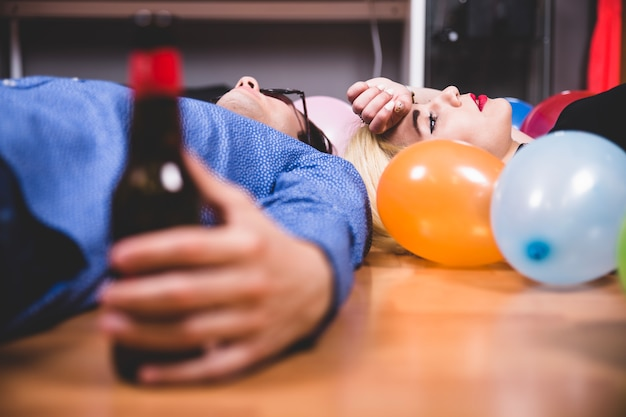 Laying down with balloons and beer
