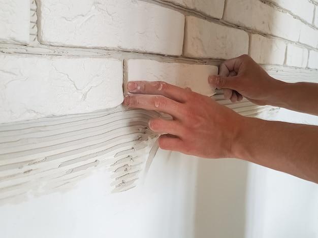 수컷 손으로 벽에 석고 타일을 일렬로 놓기. 집 수리.