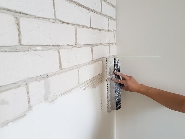 퍼티 나이프로 벽에 석고 접착제에 석고 타일을 놓습니다. 집 수리.