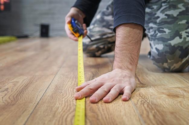 라미네이트 바닥재 깔기. 아파트 면적 측정. 수리, 건물 및 주택 개념 - 나무 바닥을 측정하는 남성 손 클로즈업