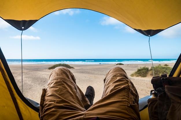 ビーチと青い海との無料キャンプでリラックスして冒険を楽しんでいるテントの中に男を置く