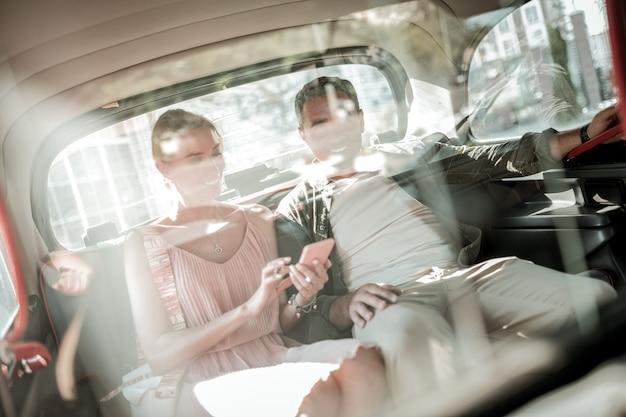 경로를 배치합니다. 쾌활한 남편과 아내는 스마트폰을 보고 있는 차 뒷좌석에 함께 앉아 있습니다.