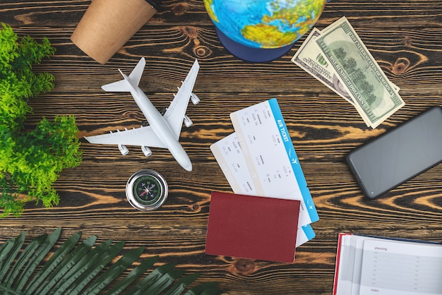 Layout of airplane travel accessories on a wooden background
