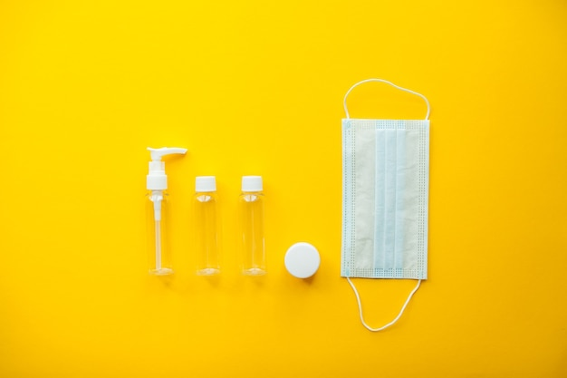 Layout on a bright yellow background cosmetic jars and protective medical mask travel set