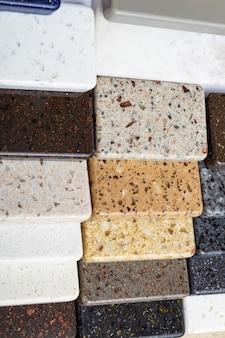 レイアウト:花崗岩、大理石、石英の天然石スラブのカラフルな標本石のキッチンカウンターのサンプルのクローズアップ