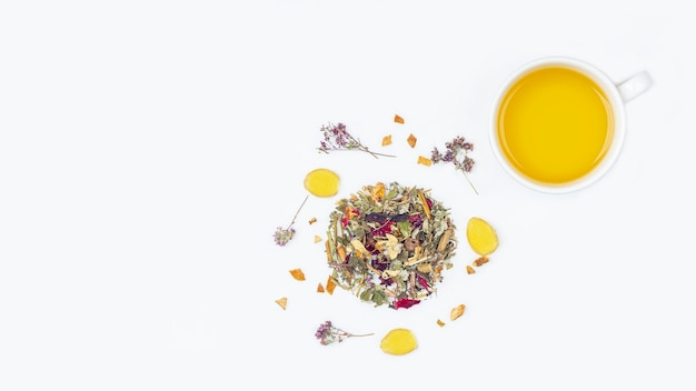Layout of cup of green tea with assortment of different dry tea leaf and flower petals on a white background