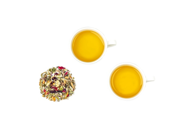 Layout of cup of green tea with assortment of different dry tea leaf and flower petals on a white
